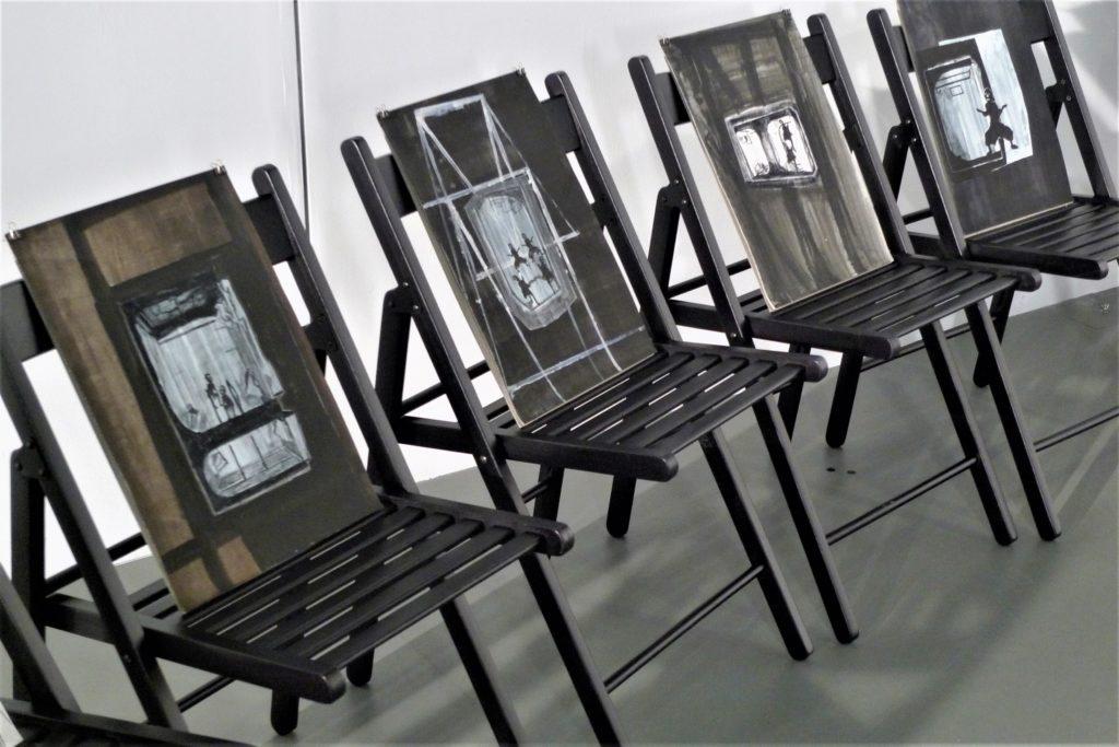 [AD: Fotografia przedstawia rząd krzeseł z umieszczonymi na nich rysunkami.]
