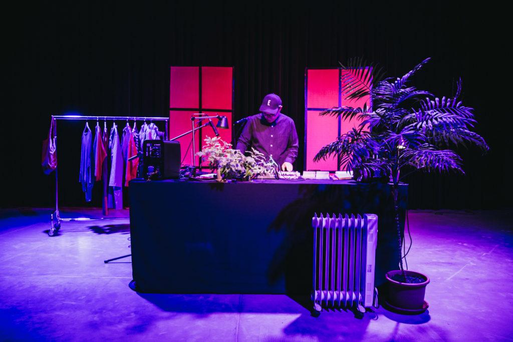 Kadr z nagrań koncertu Marcina Dymitra. Artysta stoi w sali teatralnej, przypominającej pokój.
