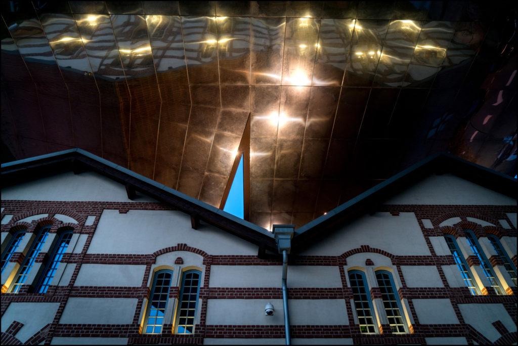 [Nocne zdjęcie budynku Cricoteki i jego odbicie w lustrzanych panelach]