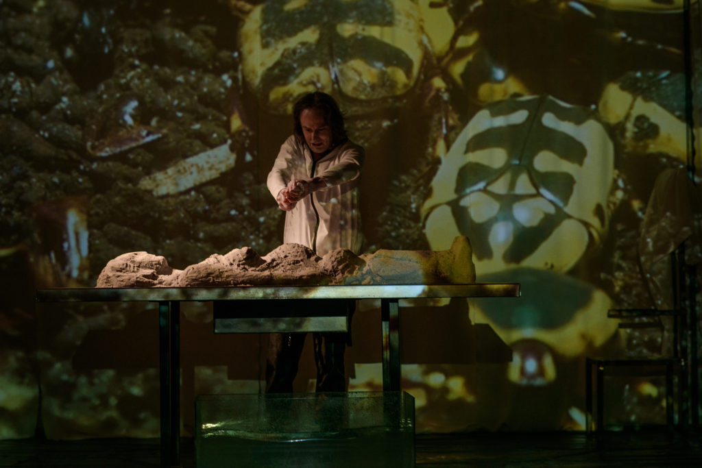 """Scena ze spektaklu """"Giaur. Aktor stojący nad stołem. Na nim usypana z pisaku góra przypominająca postać człowieka. W tle sceneria z liśćmi."""