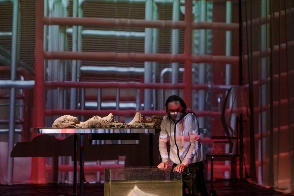 Spektakl Giaur. Mężczyzna na scenie, siedzi przed akwarium napełnionym wodą. Obok niego stół oraz leżąca na nim postać przypominająca szkielet. W tle wizualizacje barierek.