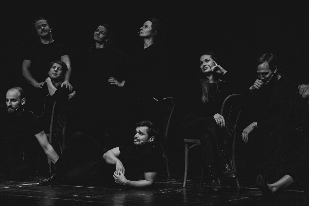 Czarno białe zdjęcie. Grupa dorosłych osób w czarnych ubraniach stoi i leży na ciemnej scenie