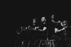 Czarno białe zdjęcie. Grupa dorosłych osób w czarnych ubraniach stoi na ciemnej scenie