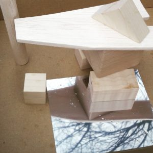 W pudełku kilka drewienek, które tworzą konstrukcję przypominającą budynek.