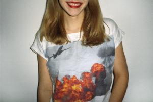 Kobieta z pomalowanymi na czerwono ustami. W koszulce, na której widać pożar, nad nim lecący samolot.