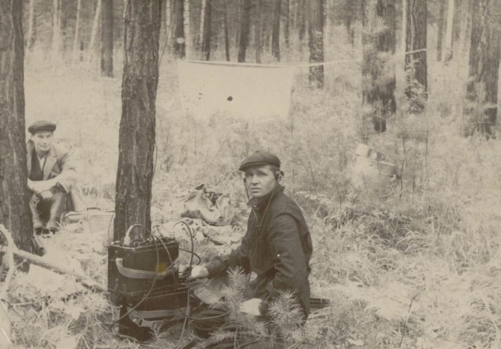 Archival photo; man sitting in the forest, looking at the photographer