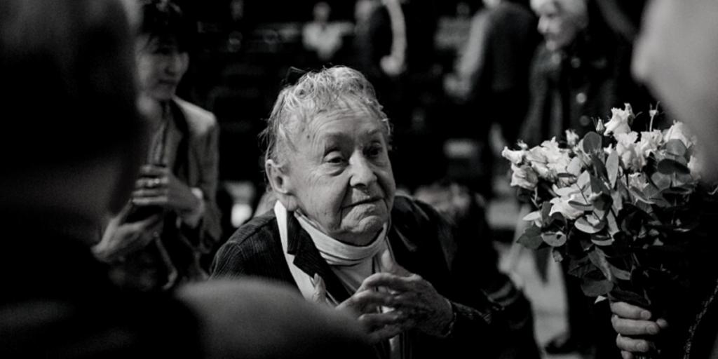Czarno białe zdjęcie starszej kobiety trzymającej kwiaty.