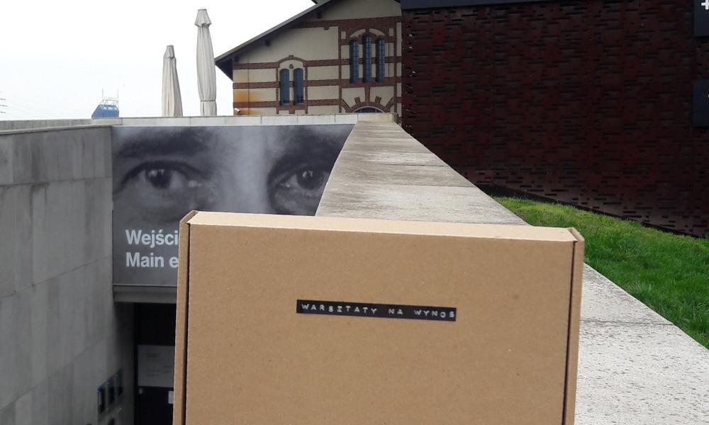 """Zdjęcie kartonowego pudełka podpisanego """"warsztaty na wynos"""". Pudełko stoi na murku przed wejściem do Cricoteki"""