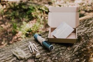 Zestaw warsztatów na wynos. Na pniu drzewa ustawione otwarte pudełko, z instrukcją w środku. Obok zwinięty w rulon materiał, manekin, włóczka.
