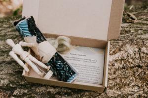 Zestaw warsztatów na wynos. Na pniu drzewa ustawione otwarte pudełko. W nim instrukcja, manekin oraz materiał.