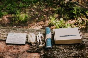 Zestaw warsztatów na wynos. Na pniu drzewa ustawione pudełko, zwinięty w rulon materiał, manekin, włóczka oraz instrukcja.