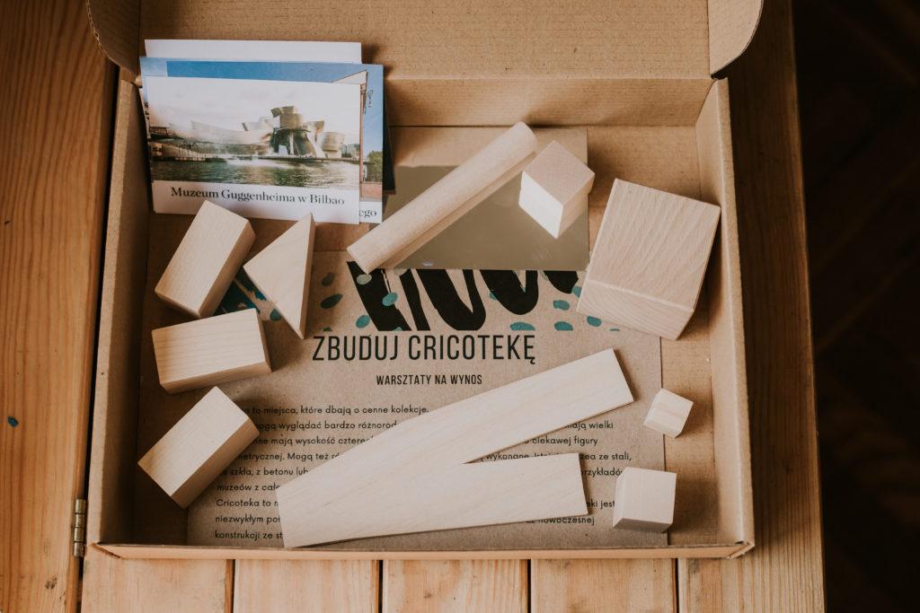 Otwarte pudełko z warsztatami na wynos. W środku drewniane klocki, zdjęcia oraz instrukcja.