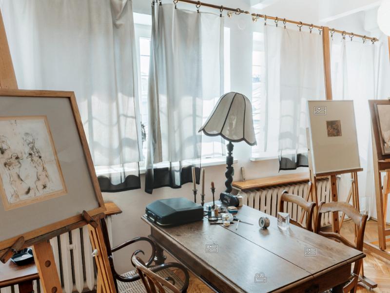 Zdjęcie z Galerii-Pracowni Tadeusza Kantora. Na stole stoi lampa oraz maszyna do pisania. Przed stołem bujany fotel. Dookoła sztalugi.