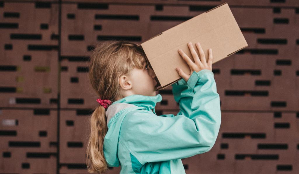 Dziewczynka trzymająca w rękach karton. Przykłada go do oczu i zagląda do środka.