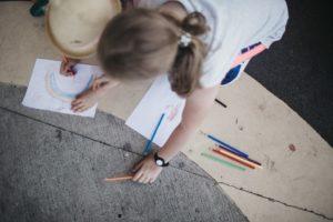 Dziewczynka siedząc na chodniku rysuje kredkami po białej kartce papieru.
