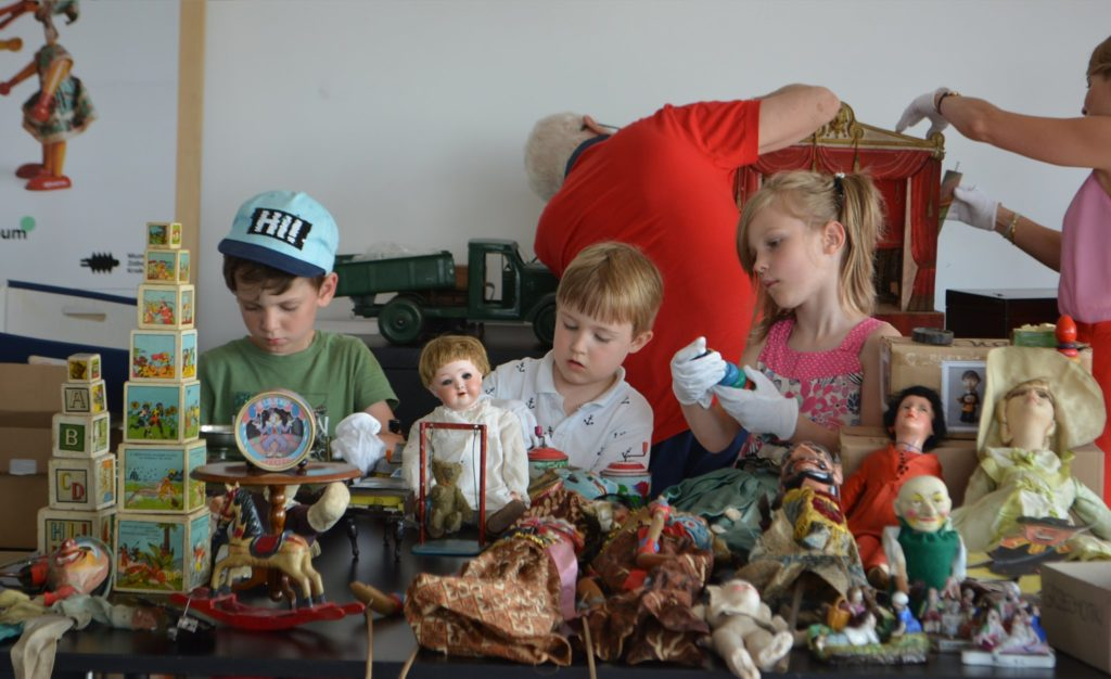 Trójka dzieci stoi przed stołem z zabawkami. Każde z nich ma białe rękawiczki, w których podnosi niektóre zabawki.