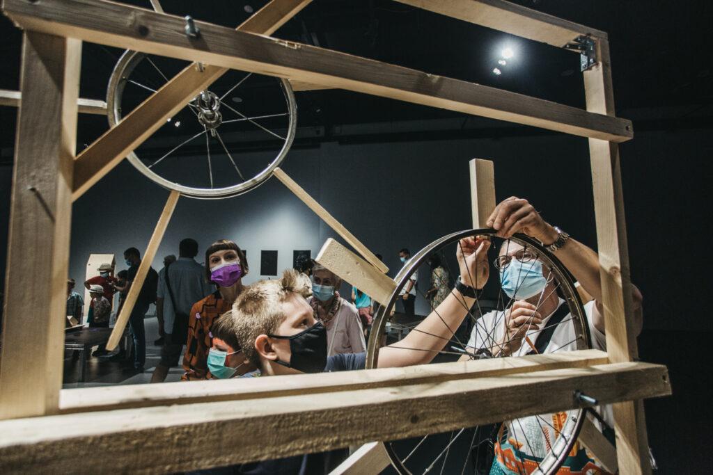 Grupa osób stoi przed drewnianą kostrukcją, w skład której wchodzi prostokątna rama i kilka kół różnego rozmiaru.