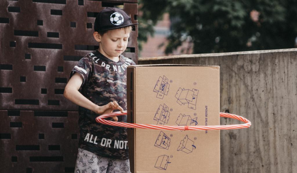 Chłopiec stojący przed budynkiem Cricoteki. Przed nim stoi karton, na który nałożone jest hula-hop