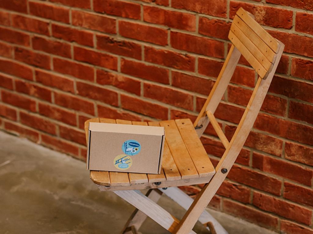 Zdjęcie kartonowego pudełka leżacego na drewnianym krzesełku