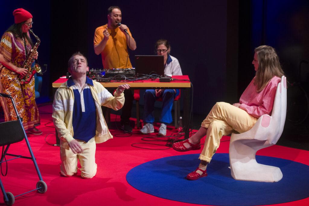 Grupa osób znajduje się na scenie. Dwie osoby grają na instrumentach, jedna śpiewa. Na pierwszym planie kobieta siedzi w krześle przypominającym dłoń.