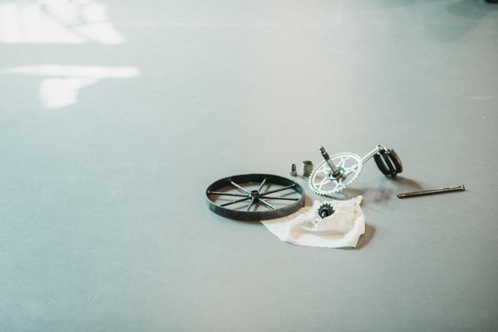 Na stole leży kilka metalowych elementów: sprężyn, kół zębatych i wkrętów.
